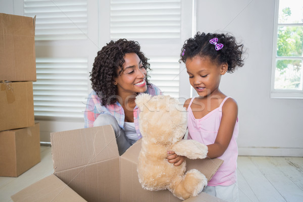 Cute daughter unpacking her teddy bear with mother Stock photo © wavebreak_media