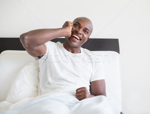 Happy man sitting in bed on the phone Stock photo © wavebreak_media