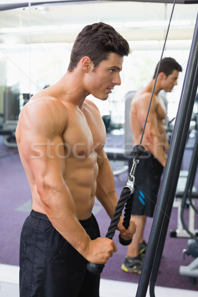 Shirtless muscular man using triceps pull down in gym Stock photo © wavebreak_media