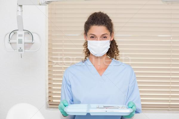Dentist in blue scrubs holding tray of tools Stock photo © wavebreak_media