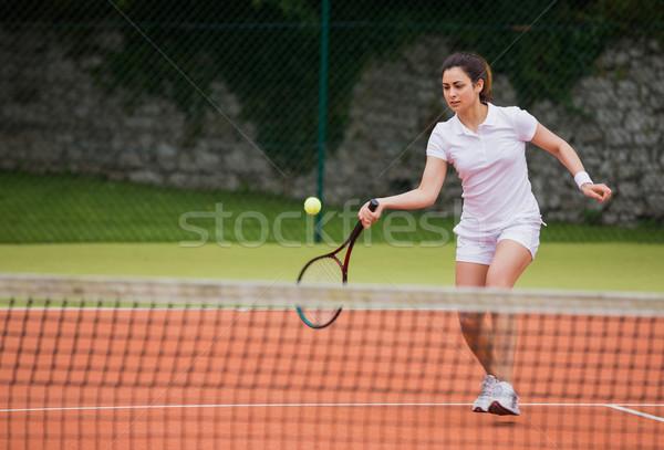 Tennis player hitting ball