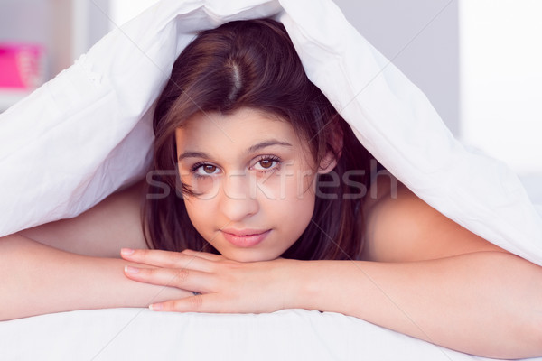 Beautiful brunette smiling at camera under duvet Stock photo © wavebreak_media