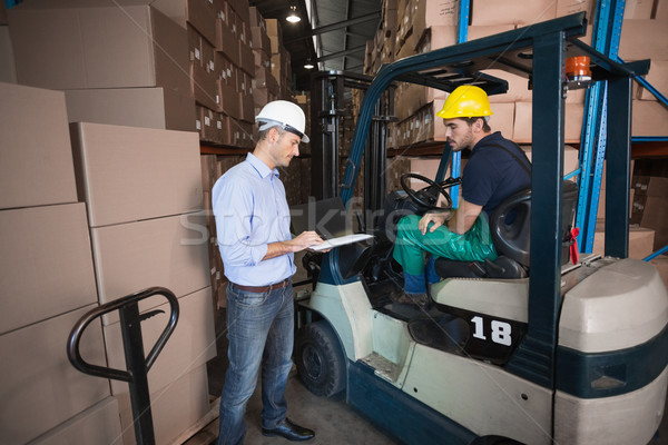 Warehouse manager talking with forklift driver Stock photo © wavebreak_media