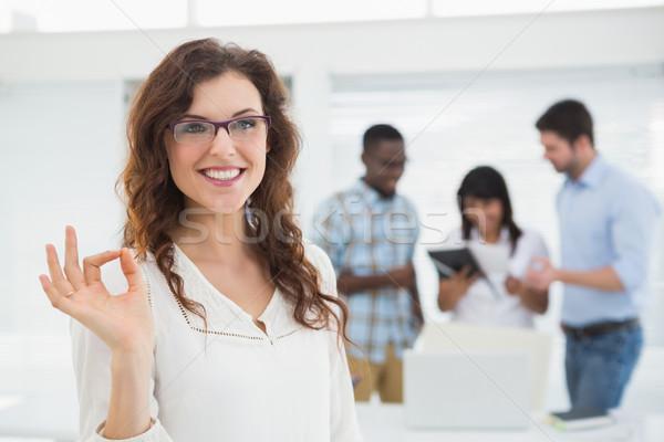 笑みを浮かべて 女性実業家 オーケー ジェスチャー 同僚 ストックフォト © wavebreak_media