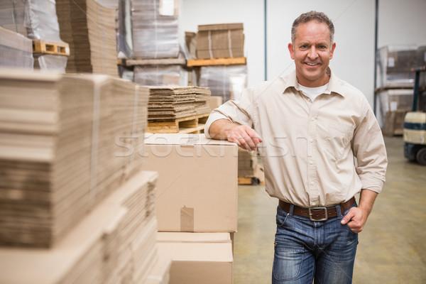 Smiling warehouse worker leaning against boxes Stock photo © wavebreak_media