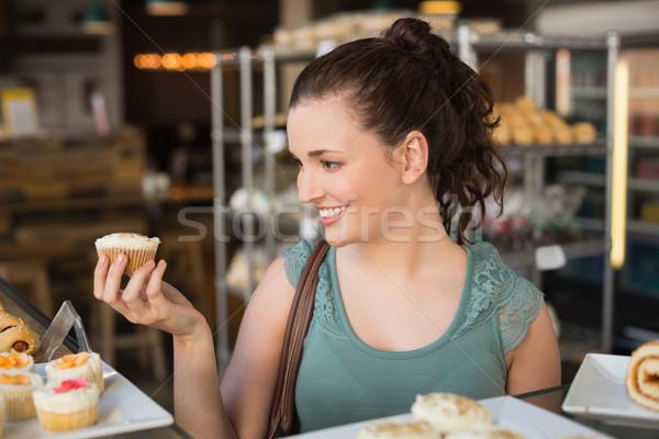 Pretty brunette holding a cupcake Stock photo © wavebreak_media
