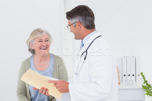 Doctor and patient conversing over reports Stock photo © wavebreak_media