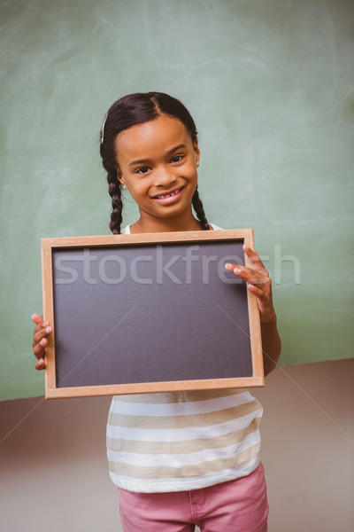 Portrait of cute little girl holding school slate Stock photo © wavebreak_media