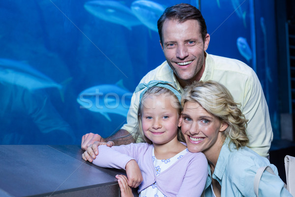 Happy family looking at camera beside the fish tank Stock photo © wavebreak_media