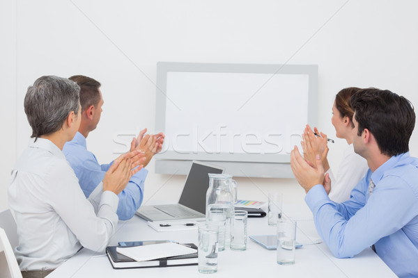 Business team applauding and looking at white screen Stock photo © wavebreak_media