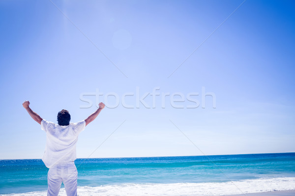 Man stretching his arms in front of the sea Stock photo © wavebreak_media