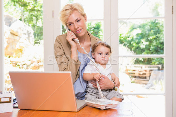 Pretty blonde woman with his son phoning and using laptop  Stock photo © wavebreak_media