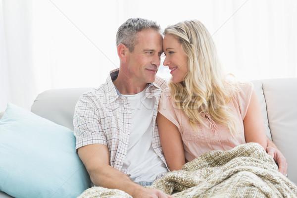 Affectionate couple sitting on sofa under blanket Stock photo © wavebreak_media