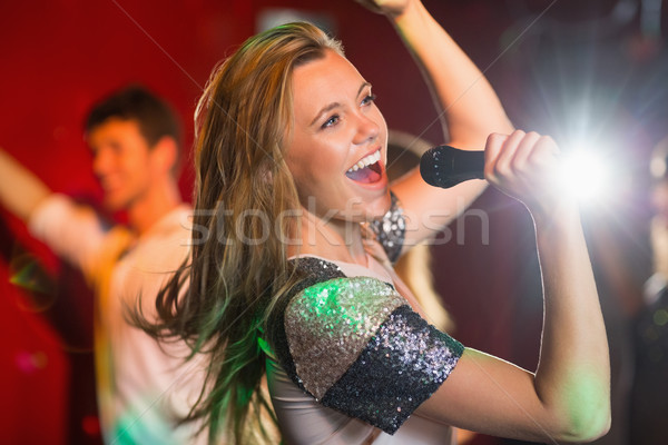 Happy blonde singing karaoke into mic Stock photo © wavebreak_media