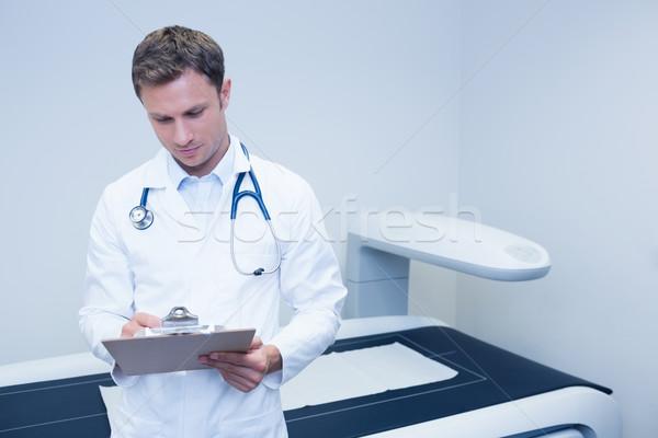 Doctor noting something on his clipboard Stock photo © wavebreak_media