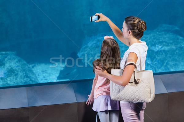 Happy mother and daughter taking photo of fish Stock photo © wavebreak_media