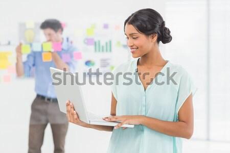 Sorridente empresária laptop tela colega Foto stock © wavebreak_media