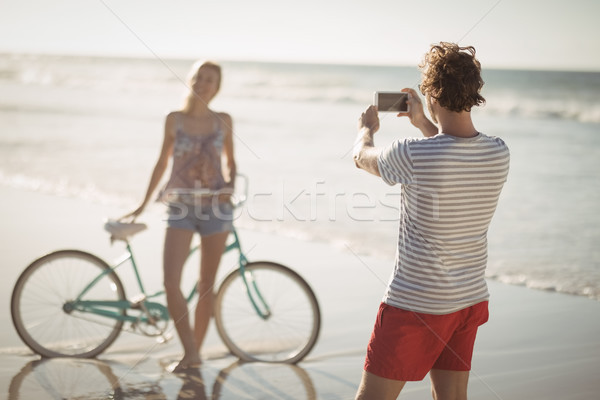 Man photographing woman standing by bicycle at beach Stock photo © wavebreak_media