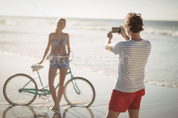 Uomo donna piedi bicicletta spiaggia Foto d'archivio © wavebreak_media