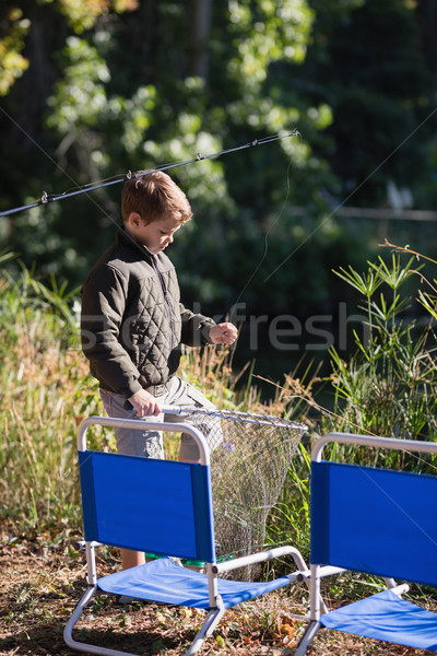 Little boy holding fishing net by chairs Stock photo © wavebreak_media