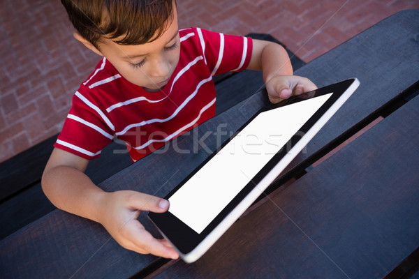 Stock photo: High angle view of boy using tablet while sitting at table