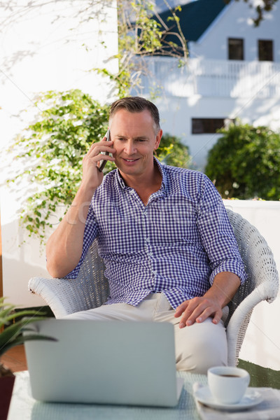 Businessman talking on mobile phone while using laptop in outdoors cafe Stock photo © wavebreak_media