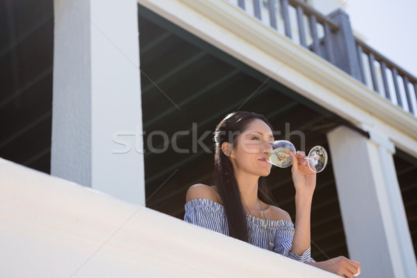 Beautiful young woman drinking white wine in balcony at restaurant Stock photo © wavebreak_media