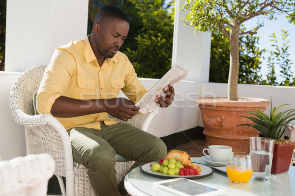 Stock photo: Young man reading newspaper by breakfast table