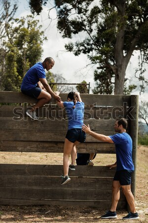 Trainer assisting a kid to climb a rope in the boot camp Stock photo © wavebreak_media