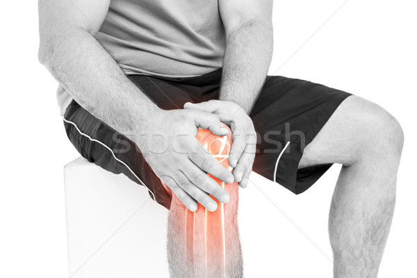 Man with knee pain sitting against white background Stock photo © wavebreak_media