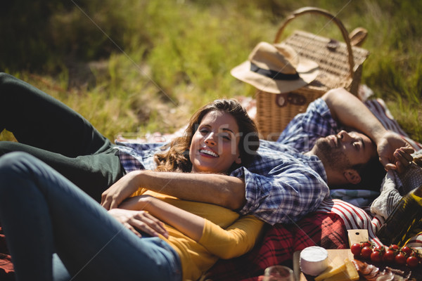 Smiling young woman with boyfriend relaxing on picnic blanket at olive farm Stock photo © wavebreak_media