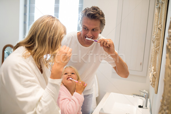 Parents and daughter brushing teeth in bathroom Stock photo © wavebreak_media