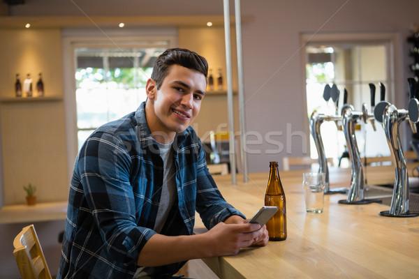 Portrait of man using phone at bar Stock photo © wavebreak_media