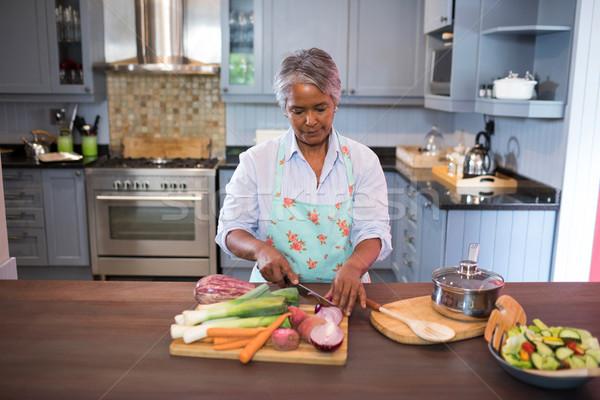 Woman cutting vegetables while preparing food Stock photo © wavebreak_media