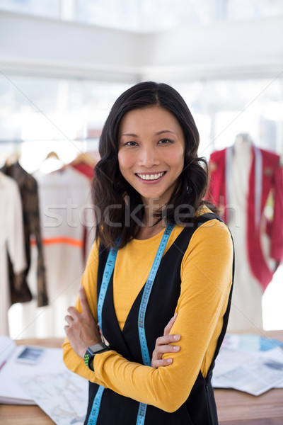 Smiling fashion designer standing with arms crossed in office Stock photo © wavebreak_media
