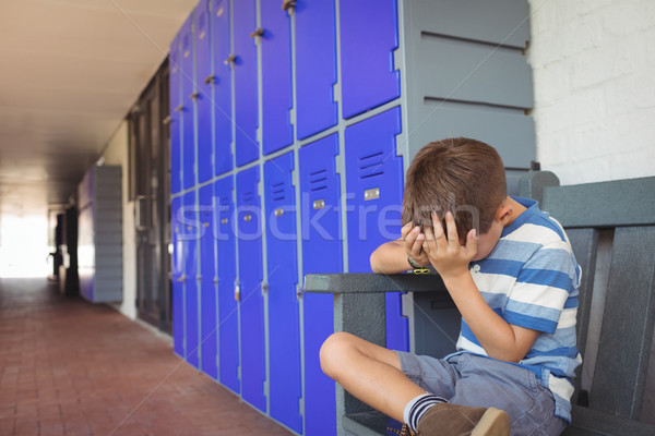 Unhappy boy sitting on bench in corridor Stock photo © wavebreak_media