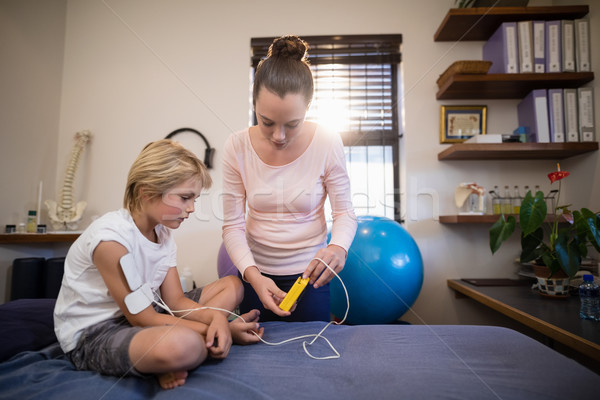 Female therapist showing electrical muscle stimulation machine to boy sitting on bed Stock photo © wavebreak_media