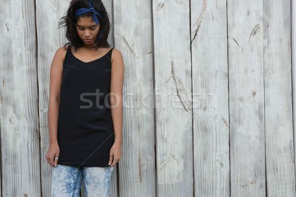 Sad woman standing against wooden wall Stock photo © wavebreak_media