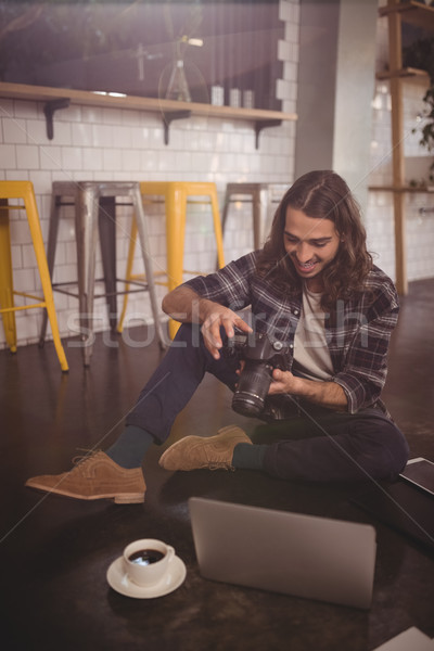 Smiling young man using DSLR camera while sitting with laptop on floor Stock photo © wavebreak_media