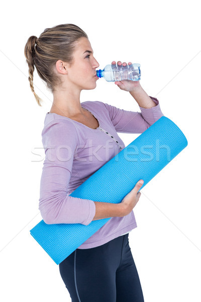 Woman drinking water while holding exercise mat Stock photo © wavebreak_media
