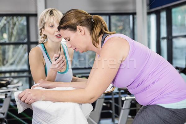 Entrenador cronógrafo mujer embarazada ejercicio moto gimnasio Foto stock © wavebreak_media