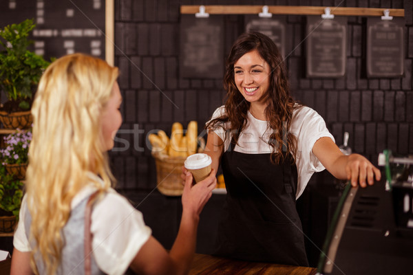 Pretty waitress giving cup of coffee to customer Stock photo © wavebreak_media
