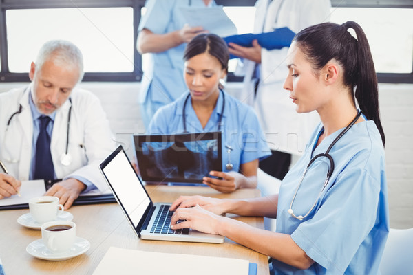 Női orvos laptopot használ konferenciaterem kollégák megvizsgál Stock fotó © wavebreak_media