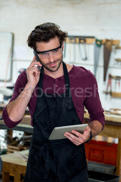 Carpenter on the phone and holding his tablet Stock photo © wavebreak_media