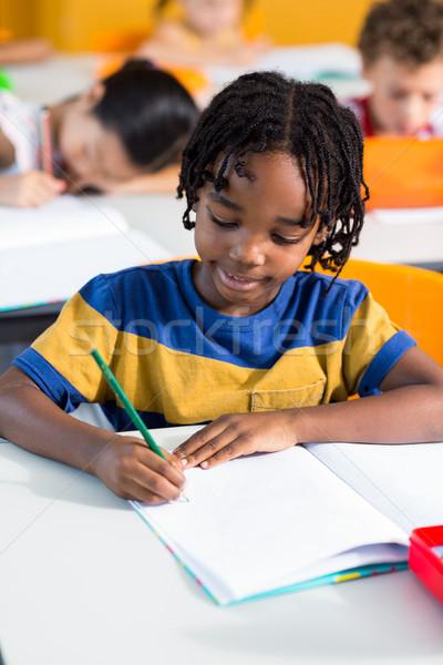 Cute boy writing on book Stock photo © wavebreak_media