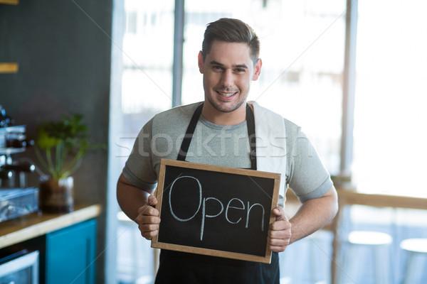 Smiling waiter showing slate with open sign Stock photo © wavebreak_media