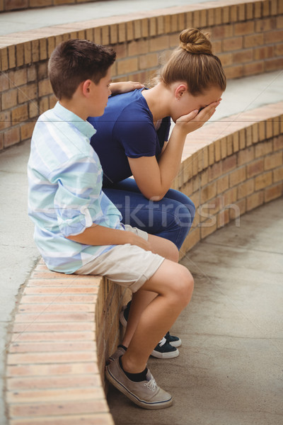 Schoolboy consoling her sad friend on steps in campus Stock photo © wavebreak_media
