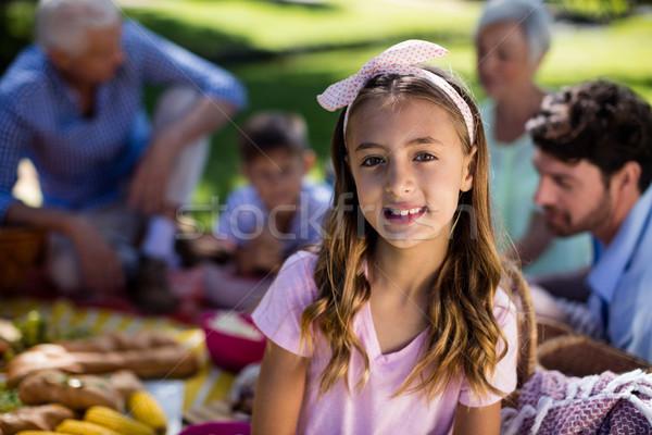 Girl with hairband and family enjoying the picnic in background Stock photo © wavebreak_media