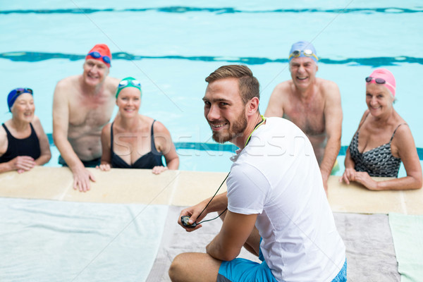 Cheerful male instructor assisting senior swimmers  Stock photo © wavebreak_media