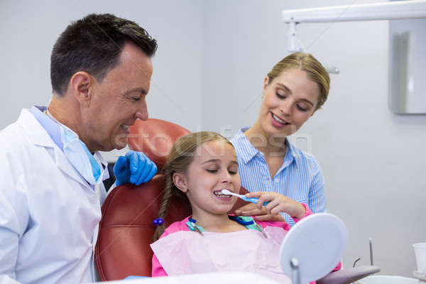Dentist assisting young patient while brushing teeth Stock photo © wavebreak_media